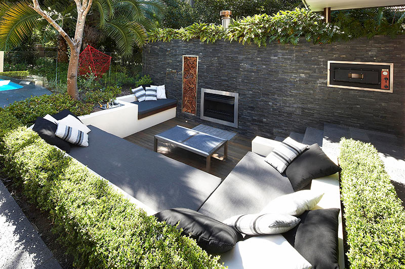 backyard-small-modern-outdoor-living-with-sunken-lounge-hedges-and-exposed-stone-wall-with-fireplace-oven-black-fabrick-sofa-and-small-garden-plants-ideas